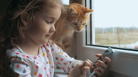 Little girl wearing blonde hair , using wi-fi on mobile phone in white case, enjoying online communication near the window. Child is playing on the smartphone. Red cat looks out the window.
