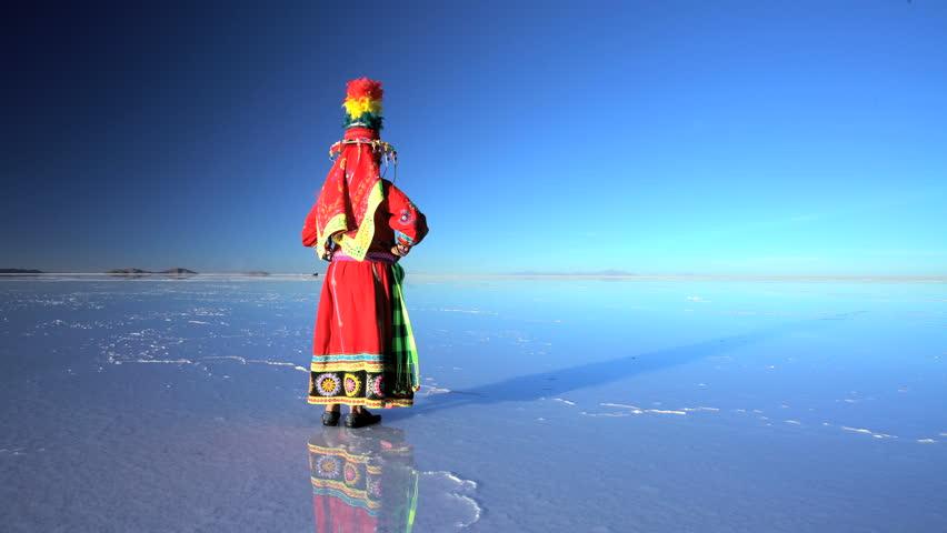 Traditionally dressed Latin American female on the Bolivian Salar de Uyuni mineral Salt flats South America