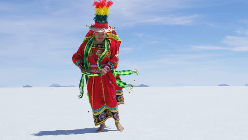 Multi coloured traditionally dress female dancing Latin American style on Salar de Uyuni Salt flats wearing traditional National costume