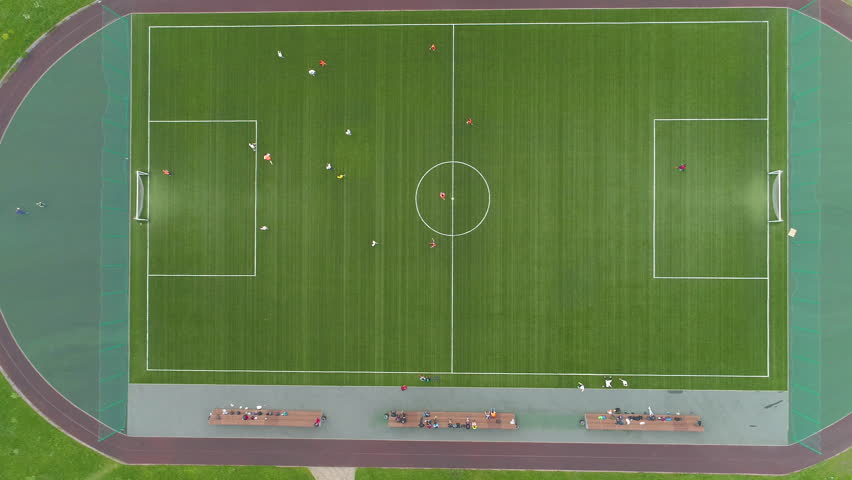 Flying over green soccer field to the right. Players playing football. Aerial vertical top view. #28193674