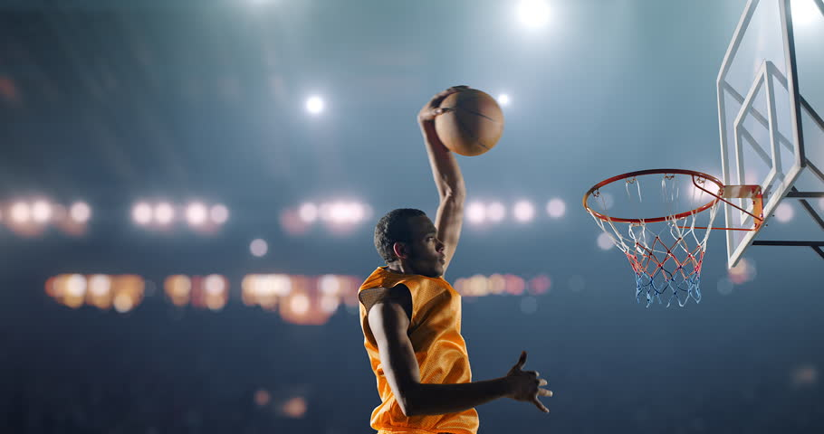 Close up image of professional basketball player making slam dunk during basketball game in floodlight basketball court. The player is wearing unbranded sport clothes.