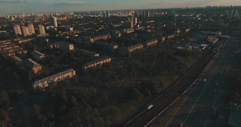 Urban landscape of the old city, aerial. Cityscape of Kiev from above. Summer evening, sunset, houses, roads and cars. People walk on the sidewalk. Green trees in the city quarter.