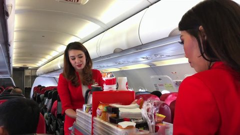 KUALA LUMPUR - JUNE 17, 2017: AirAsia air hostesses serve drinks out on board to Ho Chi Minh City. AirAsia has been the worlds best low cost carrier for 8 years including the latest award for 2016