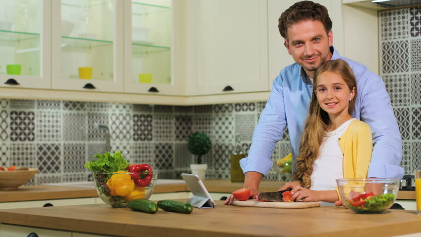 Caucasian Family In The Kitchen Making A Salad Together, Father Cutting The  Tomato, Daughter