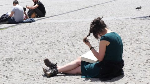 PARIS, FRANCE - MAY 23, 2017: Student Girl Sit On Pedestrian Square Cobblestone Read Leaf A Book Near Pompidou Center In Paris