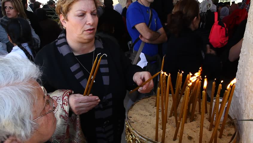 QASR AL YAHUD, ISRAEL – JANUARY 18: Greek Orthodox pilgrims lit candles at baptismal site during the Epiphany at Qasr Al Yahud, Israel, January 18 2012