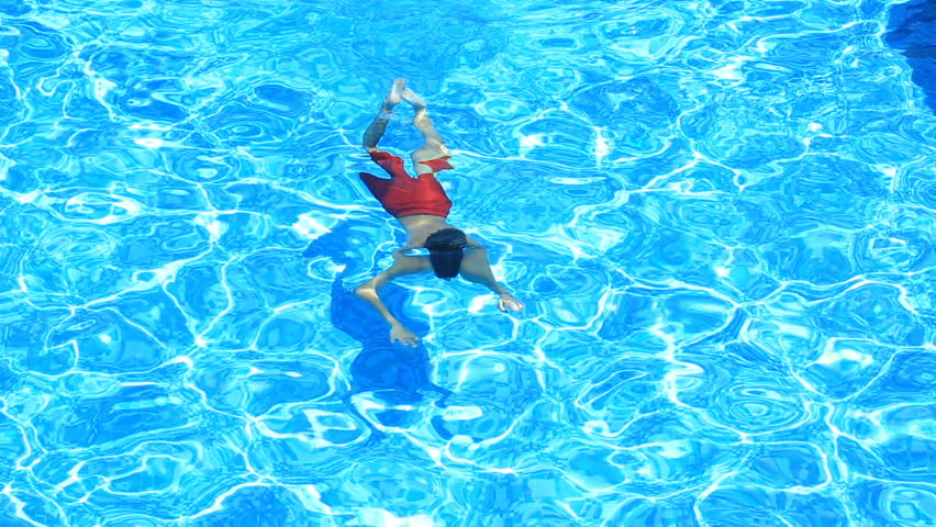 The child is swimming in the blue water of the pool. view from above. The boy dives under the water in the pool | Shutterstock HD Video #28268554