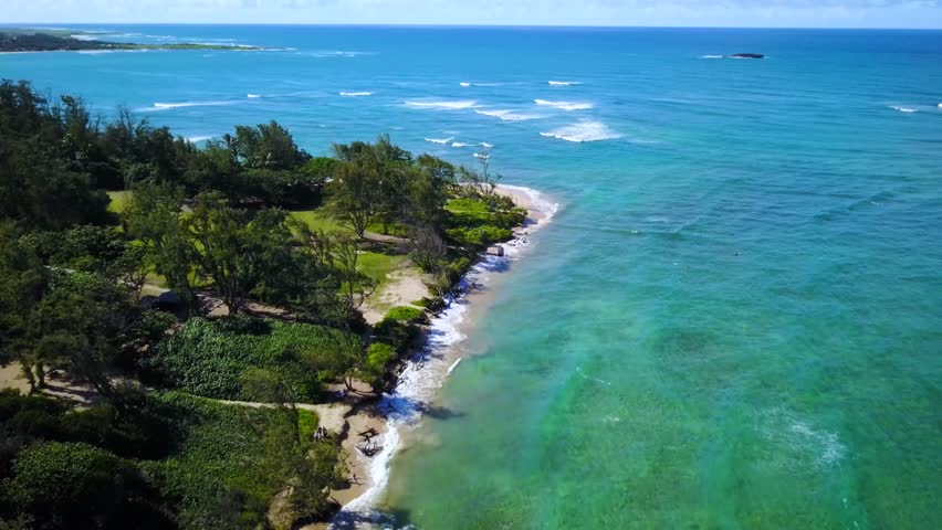 Flyover drone shot Malaekahana Beach with crystal clear ocean turquoise-blue water. Secluded Beach with long narrow strip of sand. Cinematic 4K. North Shore of Oahu Hawaii near Turtle Bay Resort.