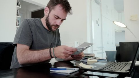Young man overwhelmed by his bills at home.A young man at home calculates his living expenses and sums his bills and his overdue notices and falls into despair