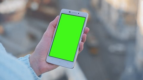 Young Woman in blue sweater sitting near window holds SmartPhone with pre-keyed green screen. Perfect for screen compositing. Made from 14bit RAW. Encoded in 10bit ProRes 444