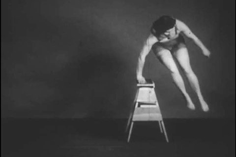 1930s: A female model demonstrates the benefits of the crouch position in attempting to jump over and onto different objects, in a film by Dr Beckett Howorth about dynamic posture.