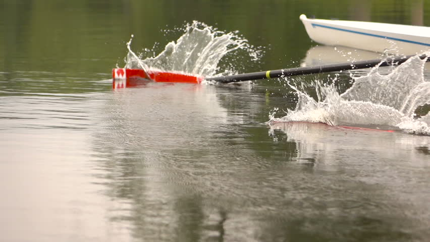 Competitions in rowing. Paddle in the water. Water splashes.