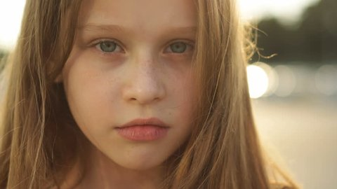 Portrait of a young girl seriously looking into the camera in the sunlight