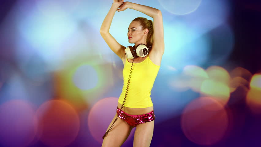 a sexy gogo dancer shot in a studio dancing agaisnt green screen with disco style background added
