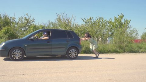 Young woman  in green dress pushing a car while man is emboldening her.Transportation, teamwork, funny concept
