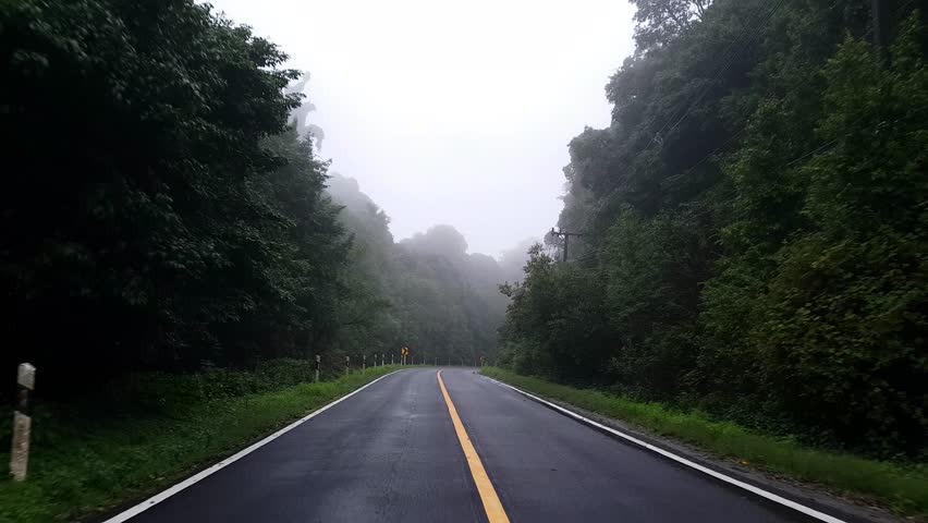 Driving along a foggy curving road through the Inthanon mountain and forest in Thailand in the morning