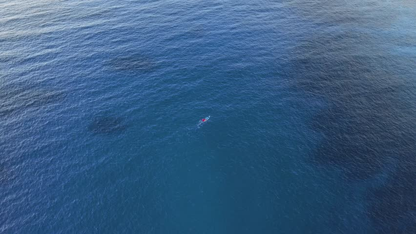 A kayak paddling over a tropical ocean from a drone