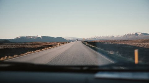 View inside the car through the windshield on beautiful countryside road with beautiful sunset, mountains landscape.