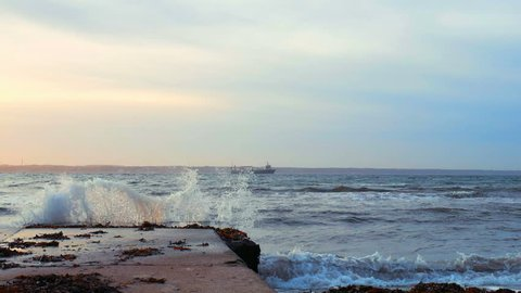 Slow motion sea waves crashing against jetty at sunset, distant cargo ship in the background