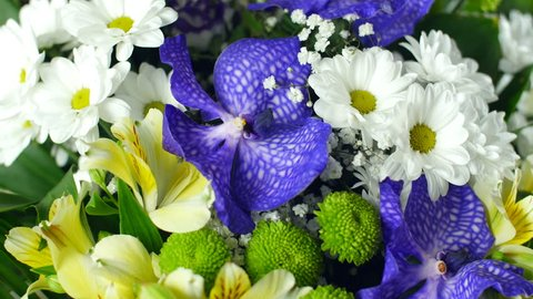 close-up, view from above, Flower bouquet in the rays of light, rotation, the floral composition consists of Alstroemeria, Chrysanthemum bacardi, Orchid vanda, Santini , gypsophila, Eustoma,