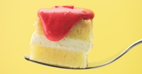 lemon cake slice on a fork with a cream and fruit topping pouring on closeup