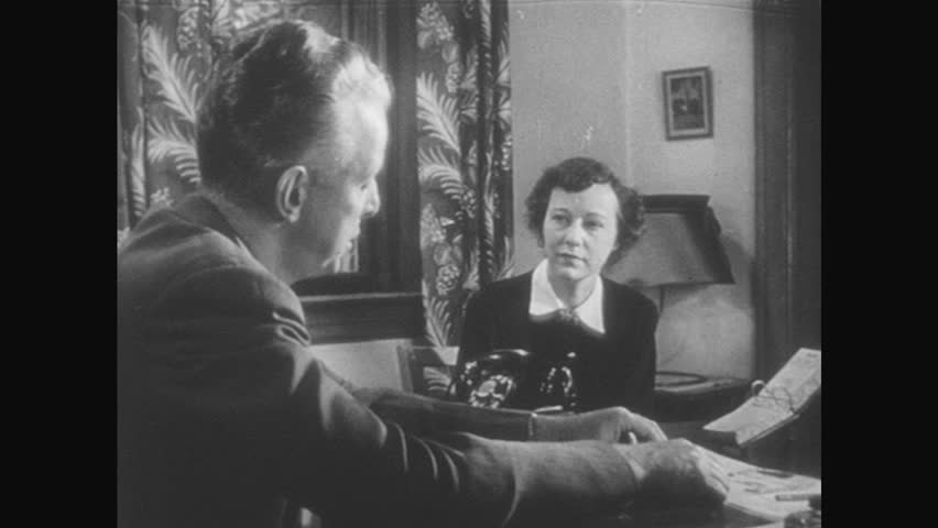 1950s: Man in office, seated at desk, talks to woman who is seated across desk, referencing papers on the desk. Brief glimpse of another woman not in the office.
