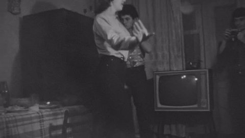 SAINT PETERSBURG, RUSSIA, 1981: Old vintage black and white film friends have party dancing in apartment living room, smoking cigarette