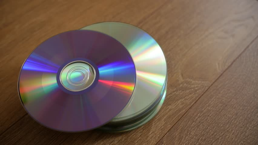 Closeup of a stack compact discs on wooden floor background. Cd falling from the top, slow-motion.