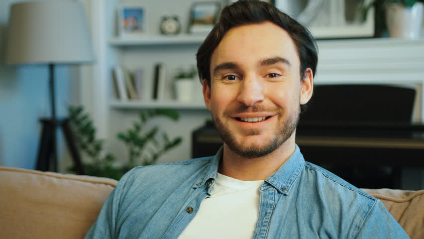 Close up portrait of young handsome man in casual blue shirt smiling on camera in the living room. | Shutterstock HD Video #28459474