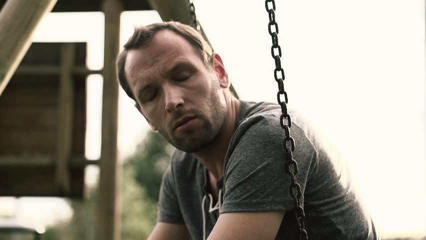 Sad, depressed man sitting on the swing, slow motion shot at 240fps