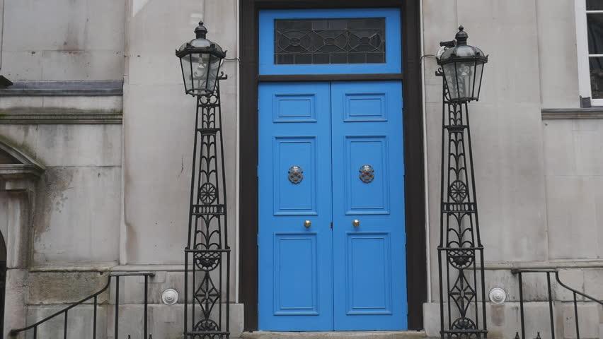 The blue door in the old gray building.