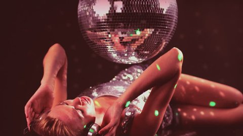 a sexy gogo dancer shot in a studio dancing and posing with a spinning discoball