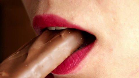 woman eating caramel, chocolate bar, close