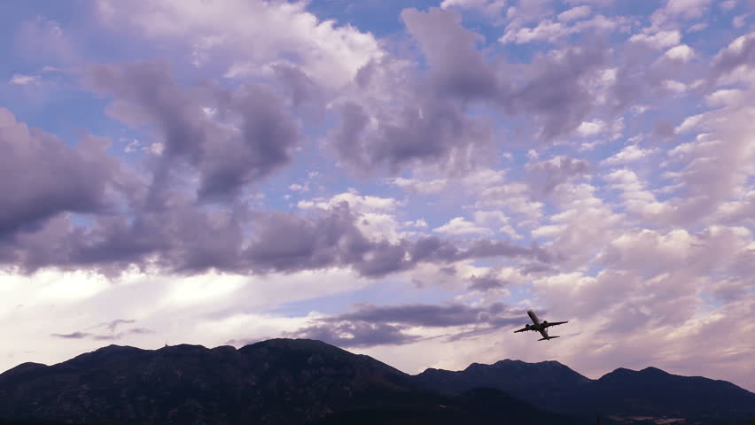 Plane takes off on the background of clouds and mountains at sunrise. | Shutterstock HD Video #28564834