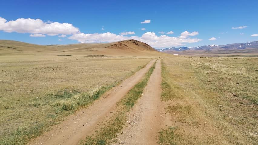 Dirt road in Chuya steppe in Altai vehicle shot