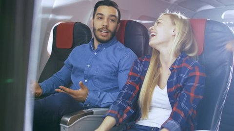 On the Commercial Plane Flight Handsome Hispanic Man Tells Funny Story to His Beautiful Blonde Girlfriend. Both Laugh. They Travel in New Airplane, with Sun Shining Through the Window. 4K UHD.