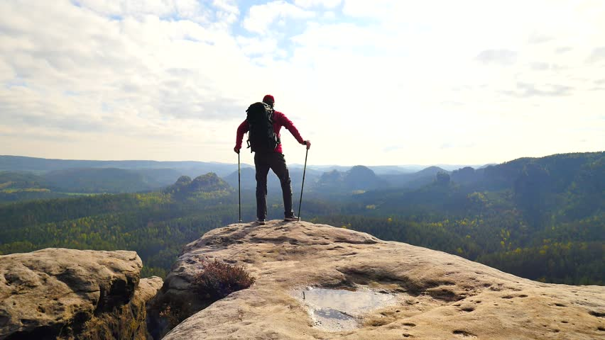 Tall tourist guide looking in paper  map. Hiker is  hiking with trekking poles and heavy backpack.  Man hiker on rocky edge check the position in the map.  Wild hilly nature park. | Shutterstock HD Video #28623556