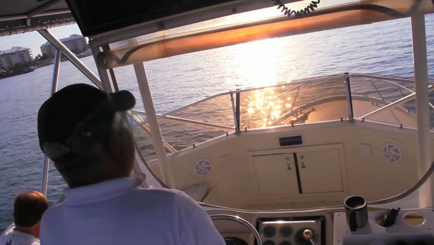 Deep Sea Fishing Captain drives boat at sunset sunrise