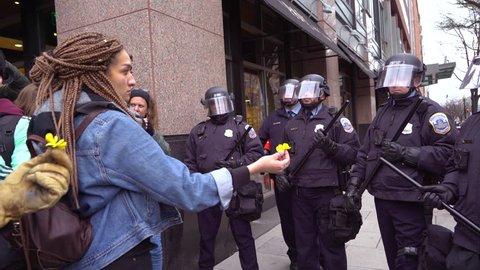 Washington D.C.-2010s: A woman offers a flower to police in riot gear at the inauguration of Donald Trump in Washington DC.