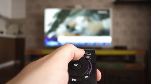 Male hand holding the TV remote control and turn off smart tv. Channel surfing, focused on the hand and remote control. Internet TV. Programm on demand.
