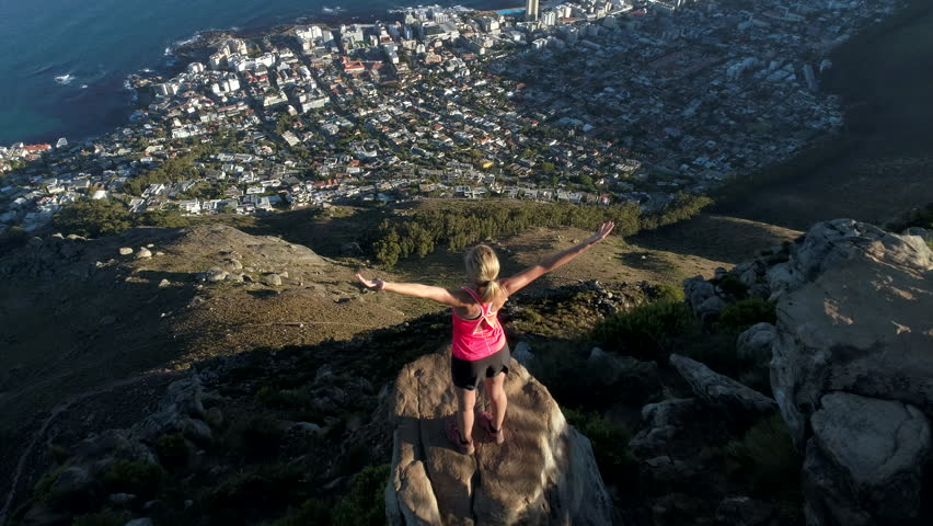 Aerial view of young woman reaching mountain top Aerial view of a young woman reaching the top of Lion's head mountain in Cape Town, South Africa.