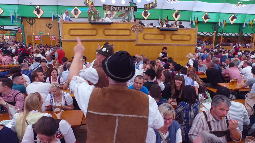 Munich, Germany-2010s: Drunken men celebrate and dance in a beer hall during Oktoberfest in Germany.