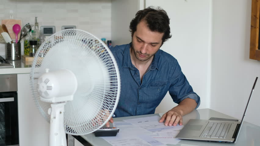 The video is about a sweaty man refreshing himself in front of a fan because of summer heat | Shutterstock HD Video #28689574