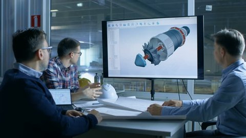 Team of Industrial Engineers Discuss 3D Model of Turbine/ Engine Design Shown on a Presentation Display. In the Background Factory is Seen. Shot on RED EPIC-W 8K Helium Cinema Camera.