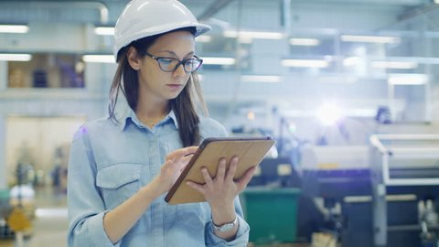 Female Industrial Engineer in a Hard Hat Uses Tablet Computer while Walking in Big Factory. Shot on RED EPIC-W 8K Helium Cinema Camera.