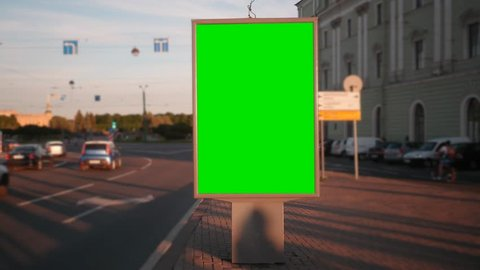 A Billboard with a Green Screen on a Busy Street