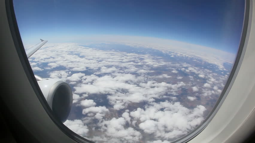 Aerial view of Europe out of an airplane window above the clouds with the earth shaped round through an fisheye view lens between Madrid and Frankfurt at daytime.