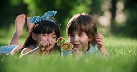 two small children,Caucasian boy and Asian girl having fun in the Park with a Lollipop