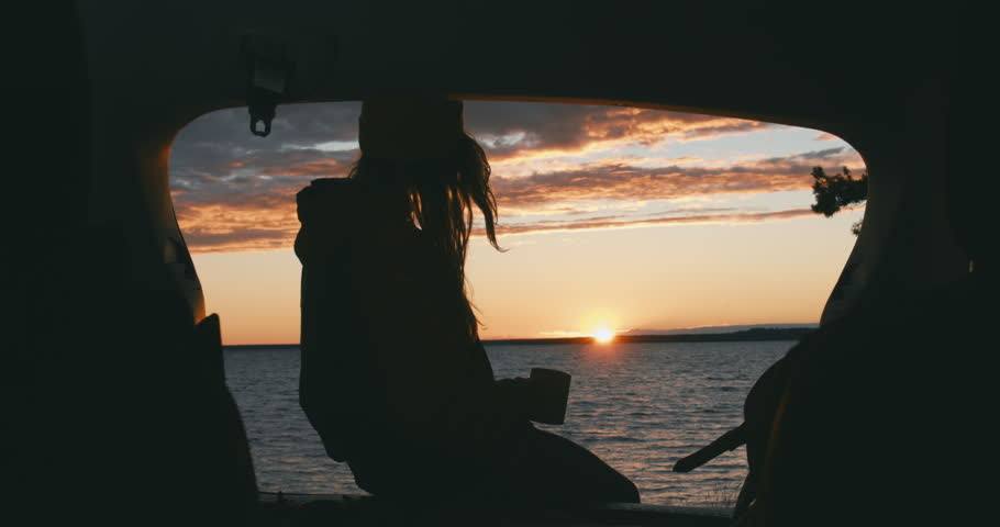 CINEMAGRAPH - seamless loop. CU Silhouette of young Caucasian female sits on a SUV trunk and enjoying hot drink on a lake during sunset. 4K UHD #28727674