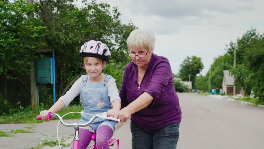 Grandmother teaches her granddaughter how to ride a bicycle. The first successes of children, activity in old age